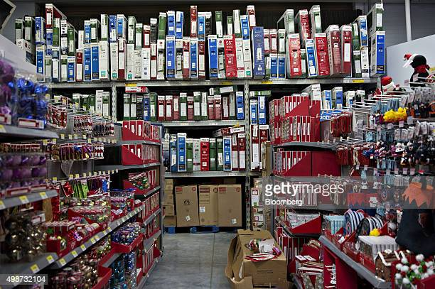 Flat screen televisions that have been put on layaway by customers line a shelf behind holiday decorations at a WalMart Stores Inc location in...