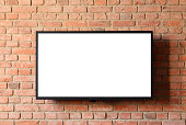Modern flat screen TV fixed on to a brick wall. Screen has been 'whited-out' ready for your additions.