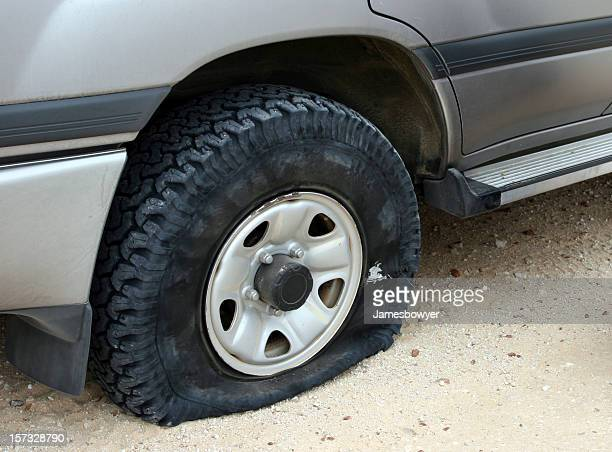 A flat tire deflating on an unpaved road