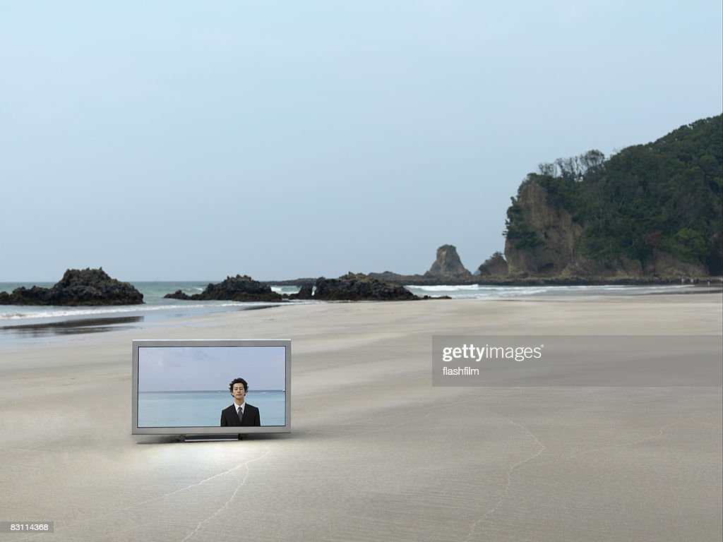 Flat TV placed on the beach : Stock Photo