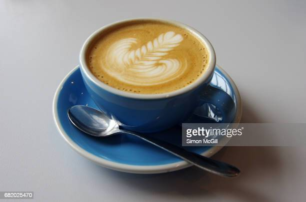 Flat white coffee in a light blue cup and saucer on a white cafe table