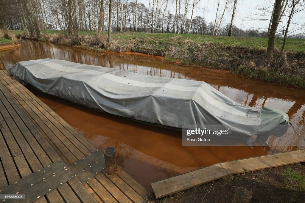 A flat-bed canoe, called a Kahn and used by a local tour operator for ferrying tourists, stands in water tinted orange due to a high content of iron sediment in the Wudritz creek in the Spreewald region on April 17, 2013 near Luebbenau, Germany. The Wudritz is heavily burdened with iron from the nearby former Schlabendorf open pit coal mine, which has since been turned into a lake called the Schlabendorfer See. Many creeks and small rivers that feed the Spree River have turned a rich orange or brown, sometimes even red, due to the sediments flowing from several former open pit coal mines. The Spreewald is a popular tourist destination known for its network of canals and local tour operators fear the sediment will turn the waters there orange as well, which could seriously impact the tourist seasons. Though the iron sediment is not poisonous, some local farmers claim they have been forced to filter the water they use to irrigate their fields, and many people report the disappearance of fish and other fauna.