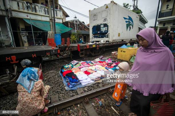 Flatbed train cars slowly make their way past Indonesians who have set up a makeshift market to sell products along a railway line in Surabaya in...