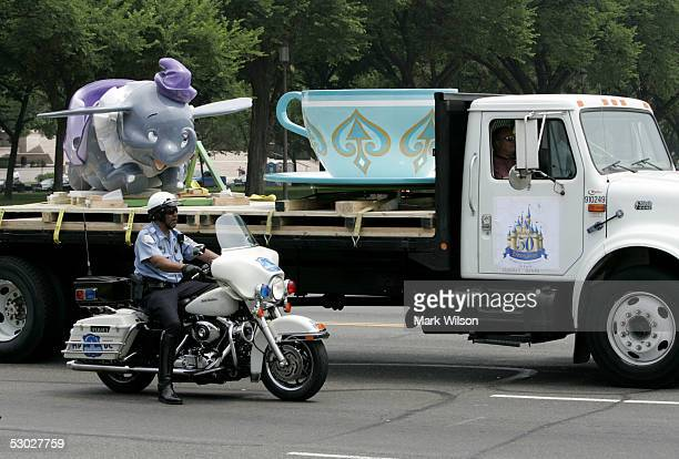 A flatbed truck carrying 'Dumbo The Flying Elephant' and a tea cup from 'Mad Hatter's Tea Party' gets a police escort past the capitol June 6 2005 in...