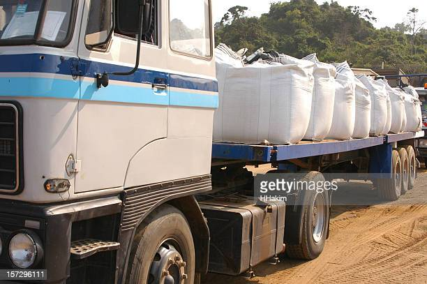 Flatbed truck loaded with white chemical sacks