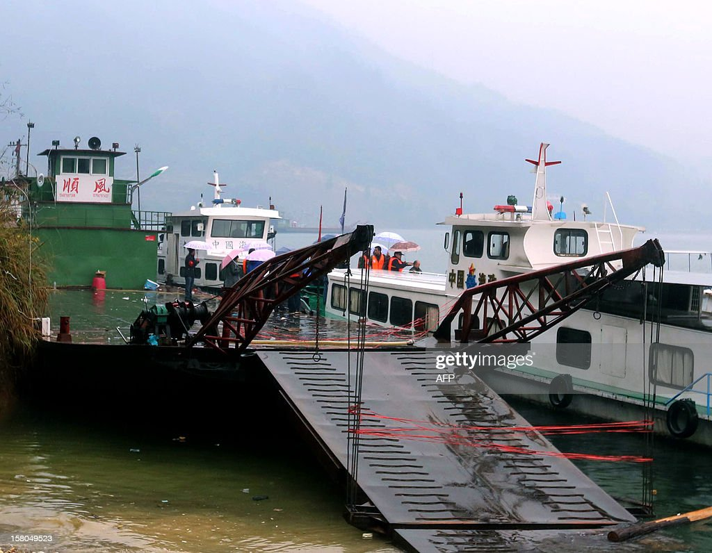 A flat-bottomed cargo boat (L) berths after being re-floated beside a rescue boat after it capsized in waters near Pingshan village in Anhua county, central China's Hunan province on December 10, 2012. Eight people have been confirmed missing after the accident takes place at around 3:40 am on December 9, four trucks the boat was hauling also sank, local authorities said. CHINA