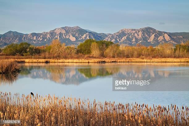 Flatirons at dawn reflecting in lake
