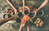 Flat-lay of friends eating and drinking together. Top view of people having party, gathering, dinner together sitting at wooden table set with wine snacks and fingerfoods. Hands with glasses clinking
