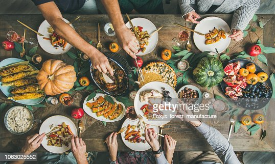 Flat-lay of friends feasting at Thanksgiving Day table with turkey : Stock Photo