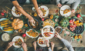 Traditional Thanksgiving or Friendsgiving holiday celebration party. Flat-lay of friends or family feasting at Thanksgiving Day festive table with turkey, pumpkin pie, roasted seasonal vegetables and