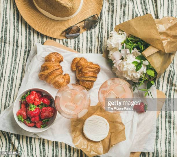 Flat-lay of rose wine, strawberries, croissants, brie cheese, flowers