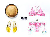 flatlay from above white beach with yellow sandals sunglasses bikini and straw hat