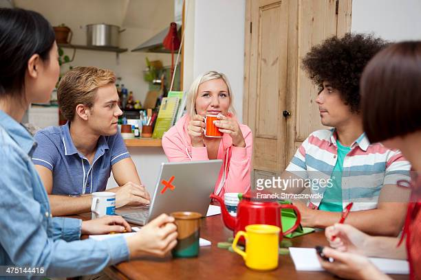 Flatmates planning around kitchen table