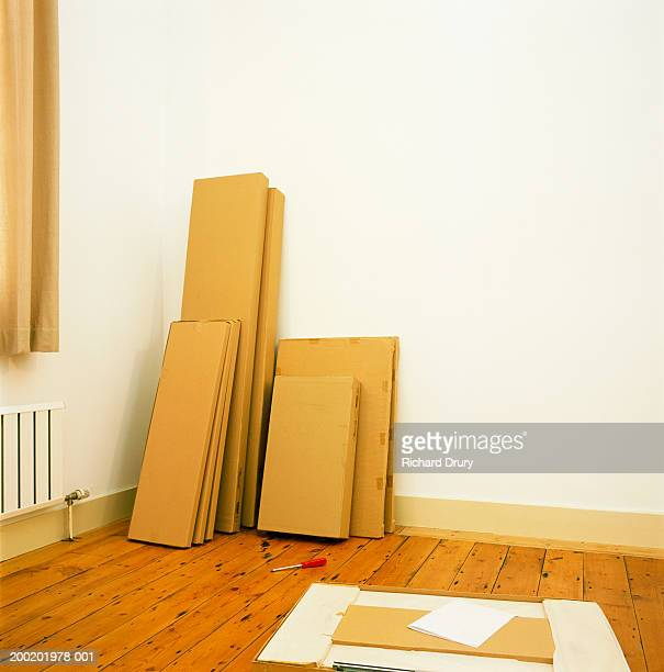 Flat-pack furniture stacked against wall, screwdriver on wooden floor
