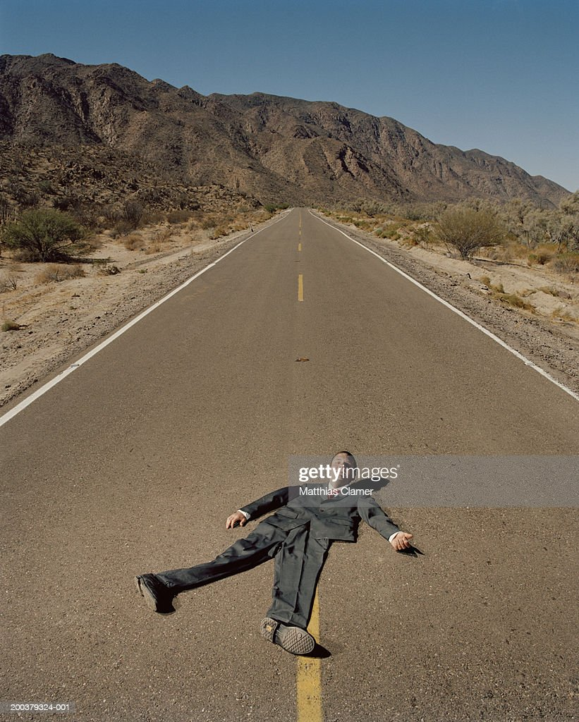 Flattened businessman on road, smiling, portrait (digital composite)