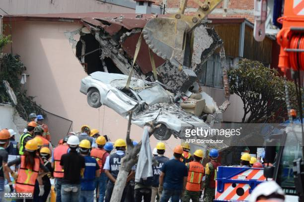 TOPSHOT A flattened car is extracted from the rubble of a collapsed building in the Roma Norte neighborhood in Mexico City on September 24 2017 Hopes...