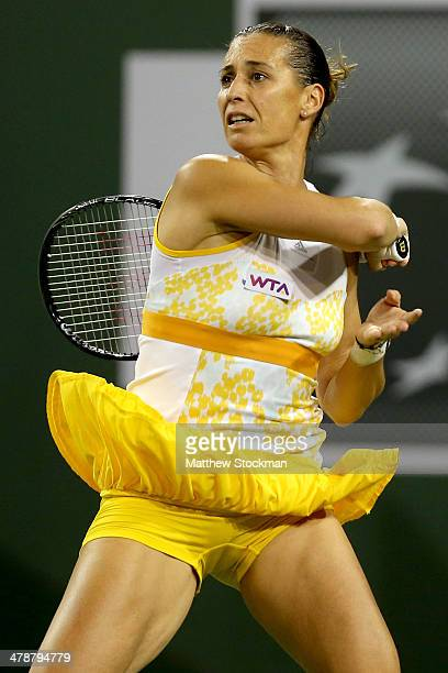 Flavia Pennetta of Italy returns a shot to Li Na of China during the semifinals of the BNP Parabas Open at the Indian Wells Tennis Garden on March 14...