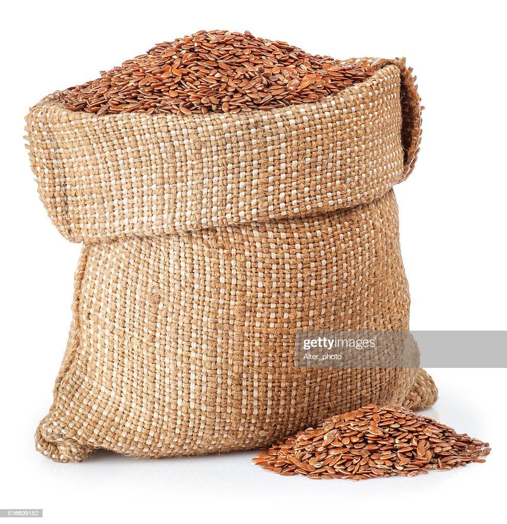 semilla de lino en bolsa de arpillera aislado sobre fondo blanco foto de stock