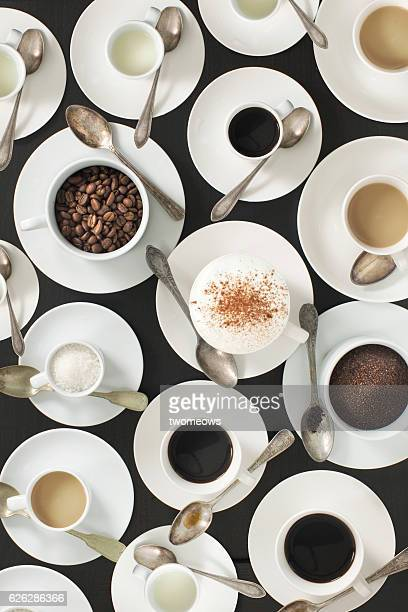 Flay lay coffee drink ingredient and different flavours in white ceramic cups.