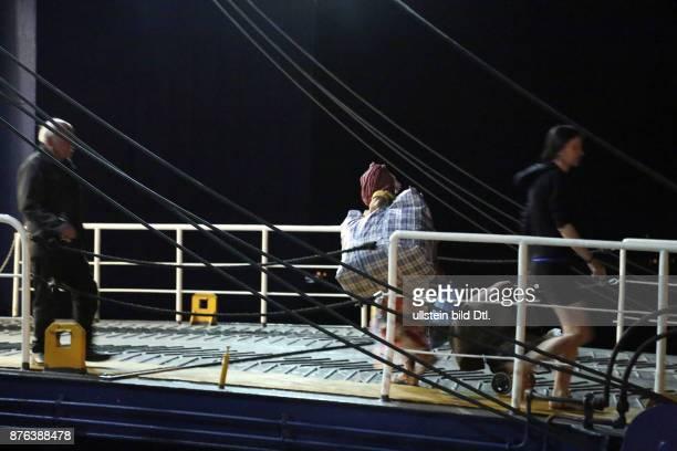 Flüchtlingsfrau mit Kopftuch geht schwer bepackt auf die Fähre in Richtung Athen Nachtaufnahme weitere Fahrgäste sind zu sehen