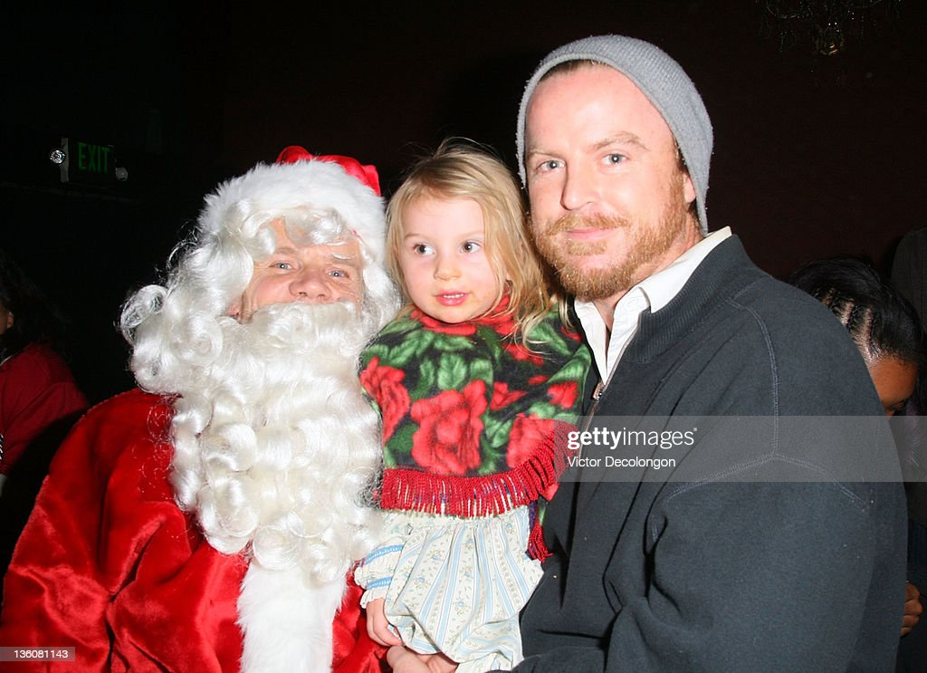 Flea (L) poses dressed as Santa Claus for a photo with Silverlake residents Amma Hollister (C) and her father Scott Hollister (R)during the Silverlake Conservatory of Music's 'Hullabaloo' Benefit Concert at El Rey Theatre on December 22, 2011 in Los Angeles, California.