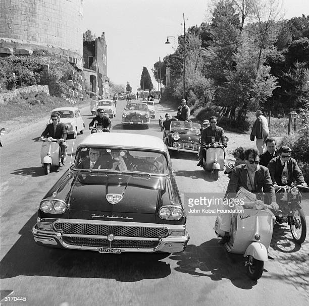 A fleet of vehicles en route to a party in a scene from 'La Dolce Vita' directed by Federico Fellini
