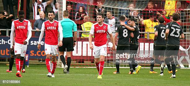 Fleetwood Town players Devante Cole Conor McLaughlin and Bobby Grant look dejected as Milton Keynes Dons celebrate after Ryan Colclough scored his...