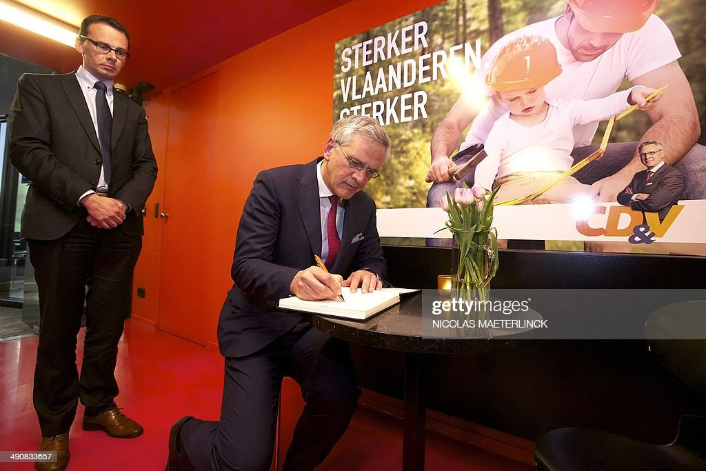 Flemish Social-Democrat CD&V party Chairman Wouter Beke (C), flanked by Flemish Minister President Kris Peeters, signs a mourning register prior to a press conference on the death of Belgium state minister <a gi-track='captionPersonalityLinkClicked' href=/galleries/search?phrase=Jean-Luc+Dehaene&family=editorial&specificpeople=2586798 ng-click='$event.stopPropagation()'>Jean-Luc Dehaene</a> at the age of 73 years old, on May 15, 2014 in Brussels. Dehaene, a former Belgian Prime Minister and chairman of the Dexia bank, passed away in France today during a visit to Brittany, due to a fall, according to a statement by the CD&V party. AFP PHOTO / BELGA / NICOLAS MAETERLINCK **Belgium Out**