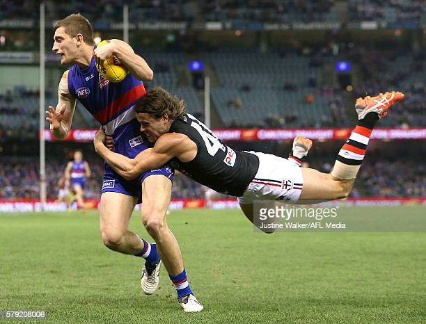 Fletcher Roberts of the Bulldogs is tackled by Maverick Weller of the Saints during the 2016 AFL Round 18 match between the Western Bulldogs and the...