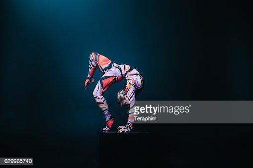 Flexible circus acrobat doing equilibre balance handstand on a cube. : Stock Photo
