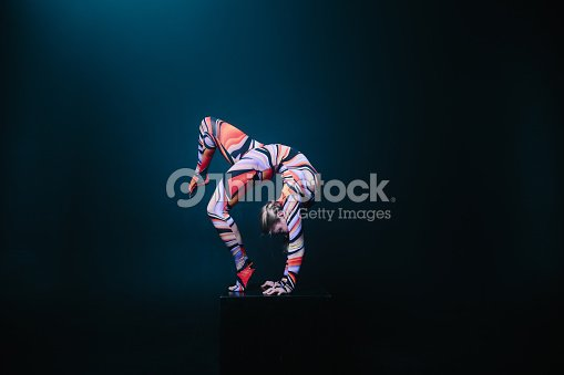 Flexible circus acrobat doing equilibre balance handstand on a cube. : Foto de stock