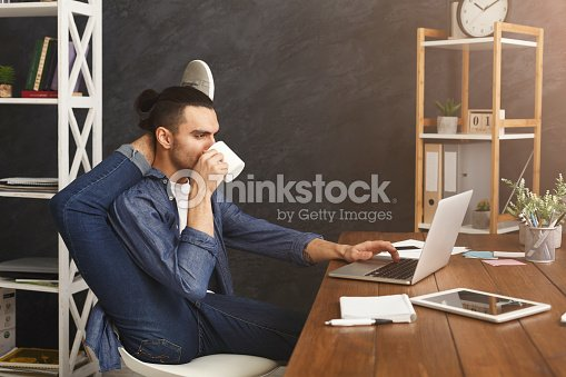 Flexible man practicing yoga at workplace : Stock Photo