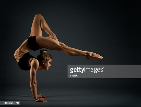 Flexible Woman Circus Gymnast, Gymnastics Hand Stand, Young Acrobat Standing on Hands, Yoga in Black Headstand Exercise : Stock Photo