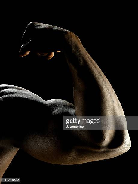 Flexing arm on black background