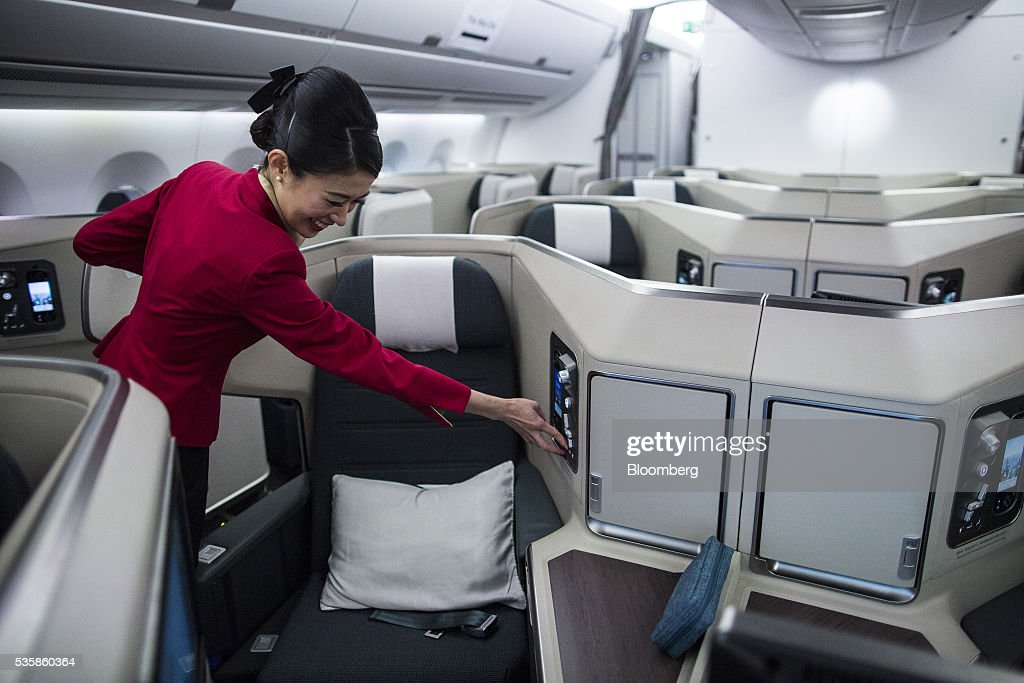 A flight attendant adjusts a business-class seat onboard an Airbus Group SE A350-900 aircraft operated by Cathay Pacific Ltd. during a media event in Hong Kong, China, on Monday, May 30, 2016. Airbus stuck to plans to increase plane deliveries this year as it pushes to overcome a series of problems affecting production of its newest aircraft. Photographer: Justin Chin/Bloomberg via Getty Images