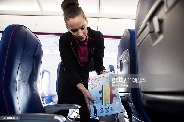 A flight attendant arranges inflight magazines onboard a passenger aircraft operated by Wizz Air Holdings Plc at Liszt Ferenc airport in Budapest...