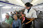 Friendly flight attendant checking on a senior couple in an airplane and looking happy - travel concepts