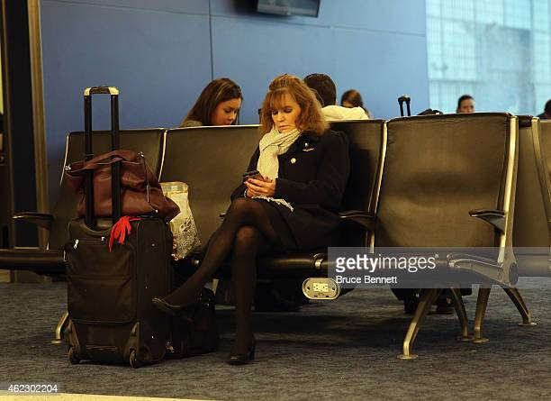 A flight attendant checks her cell phone as storm conditions worsen at Laguardia Airport on January 26 2015 in New York City Much of the Northeast is...
