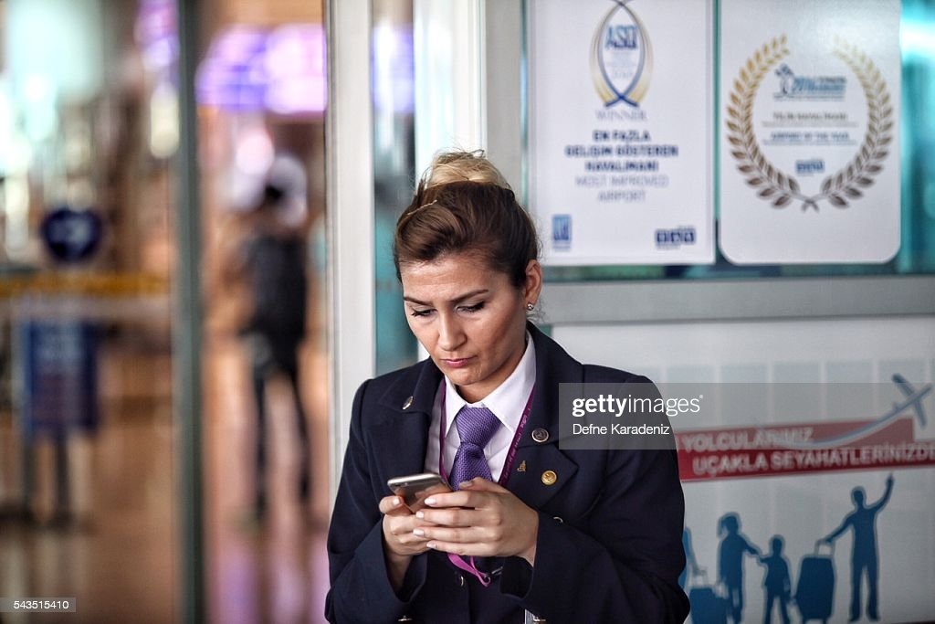 A flight attendant checks her mobile phone at Turkey's largest airport, Istanbul Ataturk, Turkey, June 29, 2016, Turkey. Three suicide bombers opened fire before blowing themselves up at the entrance to the main international airport in Istanbul yesterday, killing at least 36 people and wounding 147 people according to PM Binali Yildirim.