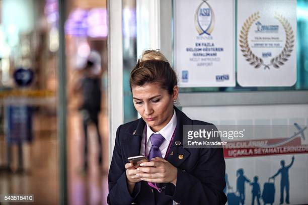 A flight attendant checks her mobile phone at Turkey's largest airport Istanbul Ataturk Turkey June 29 Turkey Three suicide bombers opened fire...