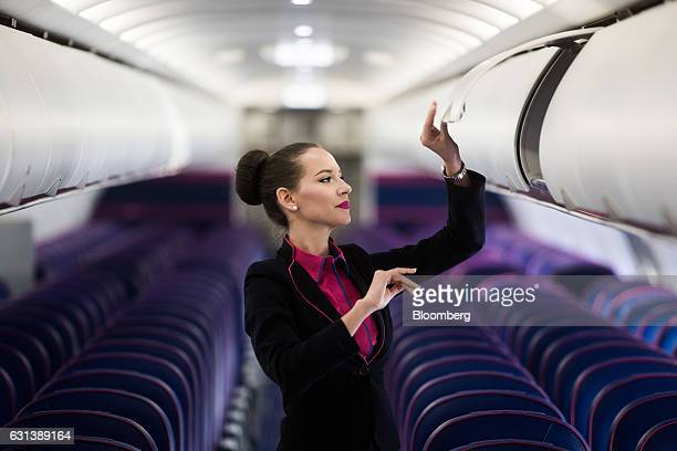 A flight attendant closes an overhead luggage compartment onboard a passenger aircraft operated by Wizz Air Holdings Plc at Liszt Ferenc airport in...