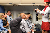 Flight attendant safety demo fastening seat belt passenger airplane cabin