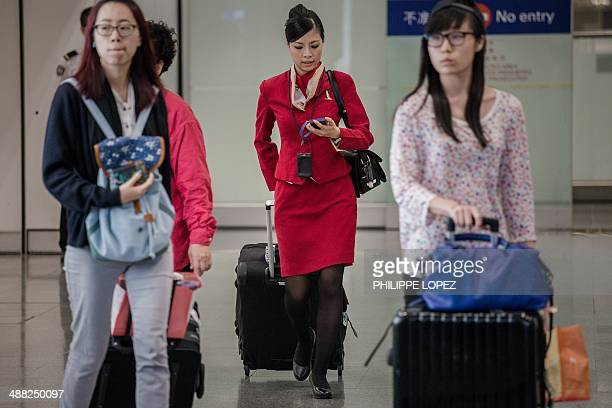 A flight attendant for Cathay Pacific checks her mobile phone after arriving at the international airport in Hong Kong on May 5 2014 Cathay Pacific...