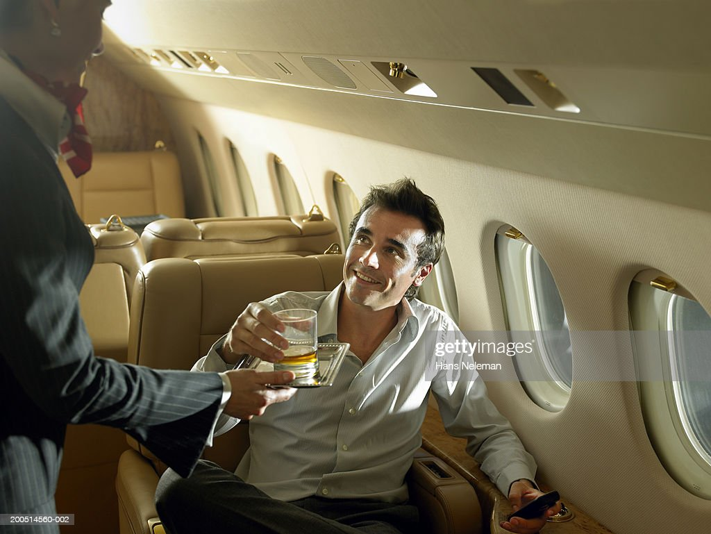 Flight attendant giving drink to businessman on private plane : Stock Photo