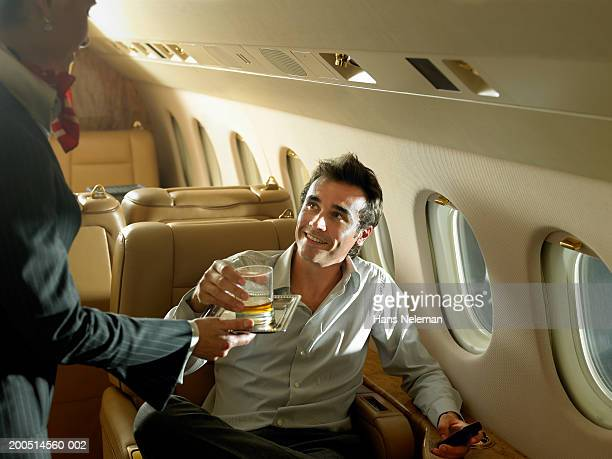 Flight attendant giving drink to businessman on private plane