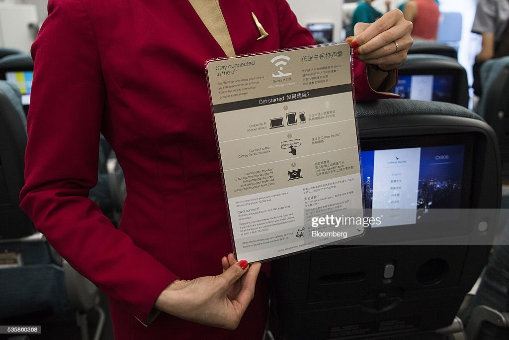 A flight attendant holds an instruction for in-flight wifi in an arranged photograph taken onboard an Airbus Group SE A350-900 aircraft operated by Cathay Pacific Ltd. during a media event in Hong Kong, China, on Monday, May 30, 2016. Airbus stuck to plans to increase plane deliveries this year as it pushes to overcome a series of problems affecting production of its newest aircraft. Photographer: Justin Chin/Bloomberg via Getty Images