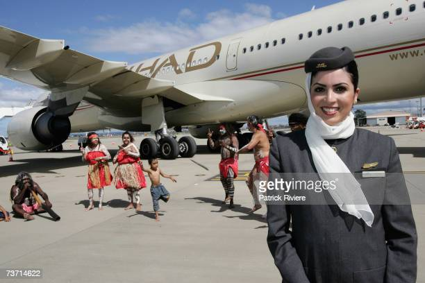Flight attendant Imtime Haddad poses with members of the aboriginal dance group Descendance during the launch of the first flight from Etihad Airways...