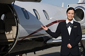 Female Asian mid-adult flight attendant in front of private jet.