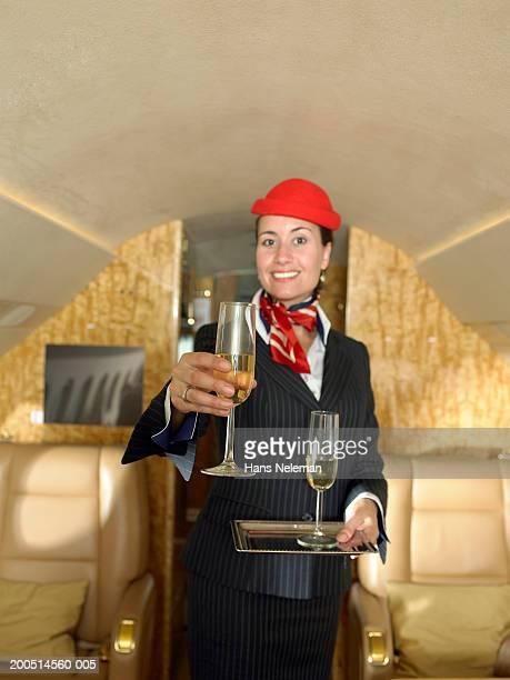 Flight attendant serving champagne, portrait
