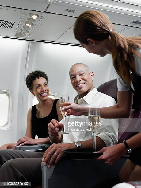 Flight attendant serving champagne to mature couple